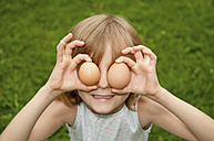 Germany, Brandenburg, Girl holding egg in front of eyes - BFRF000011