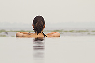 India, Kerala, Young woman relaxing in pool - MBEF000504