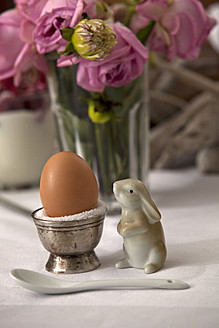 Egg in egg cup with rabbit figure, glass of flowers in background - KRF000026
