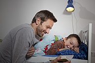 Germany, Berlin, Father reading book while son sleeping - RBF000947
