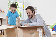 Germany, Berlin, Father and son opening parcel box - RBF000956