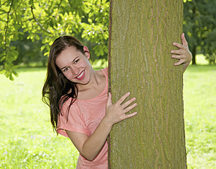 Germany, Berlin, Young woman embracing tree trunk, smiling, portrait - BFRF000060