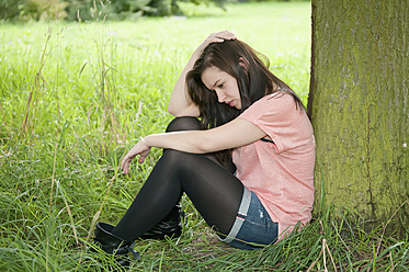 Germany, Berlin, Young woman daydreaming in park - BFRF000063