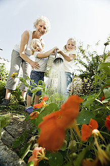 Germany, Bavaria, Grandmother with children watering flowers - RNF001028