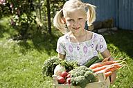 Germany, Bavaria, Girl holding vegetables in crate, smiling, portrait - RNF001040