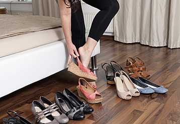 Germany, Berlin, Young woman trying on shoes - BFRF000065