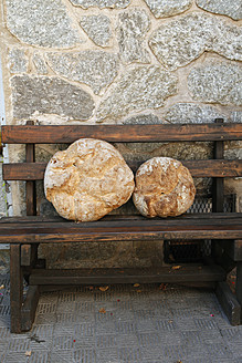 Spain, White bread loaf on wooden bench - JMF000208