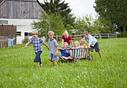 Germany, Bavaria, Group of children playing with hand cart in front of farmhouse - HSIYF000027