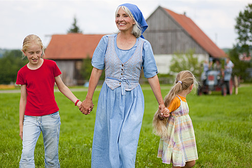 Germany, Bavaria, Grandmother with children walking in front of farmhouse - HSIYF000036