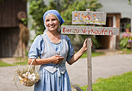 Germany, Bavaria, Mature woman standing next to sign board - HSIYF000043
