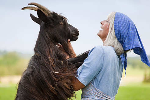 Germany, Bavaria, Mature woman with goat on farm - HSIYF000059