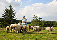 Germany, Bavaria, Mature woman caressing sheep on farm - HSIYF000062