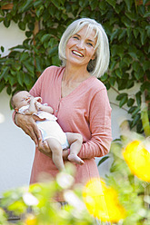 Germany, Bavaria, Woman with grandchild in her garden, smiling - HSIYF000089