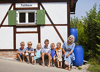 Germany, Bavaria, Woman sitting with group of children in front of small house - HSIYF000113