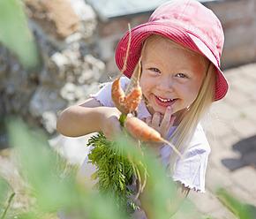Germany, Bavaria, Girl picking carrots in garden - HSIYF000126