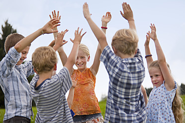 Germany, Bavaria, Group of children raising hands in air - HSIYF000151