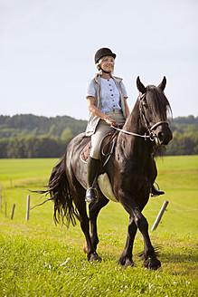 Germany, Bavaria, Mature woman riding horse - HSIYF000097