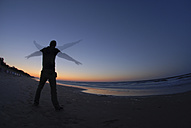 Germany, Man flapping his arms at Baltic Sea - FD000012