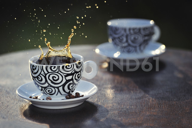 Coffee splashing out of cup, coffee beans in saucer - FDF000006