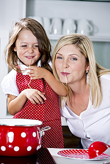 Germany, Mother and daughter eating noodles in kitchen - RFF000056