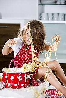 Germany, Girl playing with spaghetti on kitchen worktop - RFF000068