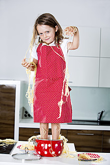 Germany, Girl playing with spaghetti on kitchen worktop - RFF000071