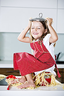 Germany, Girl playing with spaghetti on kitchen worktop - RFF000074