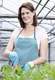 Germany, Bavaria, Munich, Mature woman in greenhouse with rocket plants - RREF000005