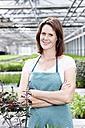 Germany, Bavaria, Munich, Mature woman in greenhouse, smiling, portrait - RREF000006