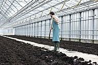 Germany, Bavaria, Munich, Mature man digging soil with garden fork in greenhouse - RREF000041