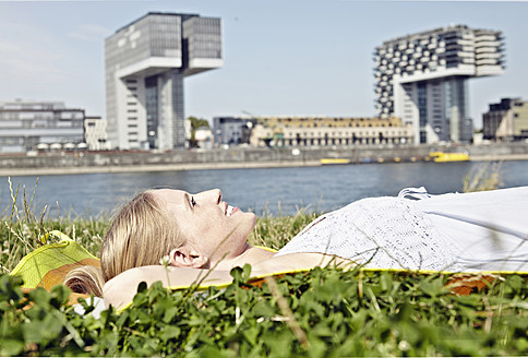 Germany, Cologne, Young woman relaxing in grass - RHYF000206