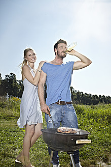 Germany, Cologne, Young couple grilling sausage and drinking beer - RHYF000220