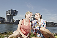 Germany, Cologne, Young women drinking beer - RHYF000262