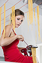 Germany, Young woman making pasta with machine - RFMYF000054