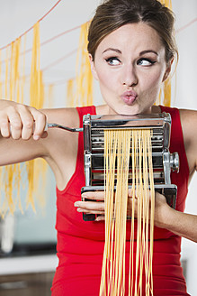 Germany, Young woman making pasta with machine - RFMYF000049