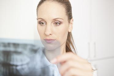 Germany, Dentist looking at dental x-rays - FMKYF000174