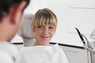 Germany, Young woman in dentist chair, smiling - FMKYF000198