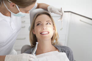 Germany, Young woman getting her teeth examined by dentist - FMKYF000213