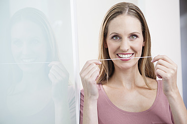 Germany, Close up of young woman holding dental floss - FMKYF000231