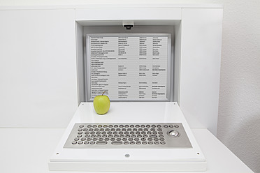 Germany, Apple on keyboard and screen installed in furniture - FMKYF000249