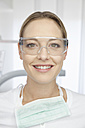 Germany, Dentist with safety glasses in dental office - FMKYF000255