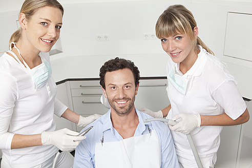 Germany, Mid adult man getting his teeth examined by dentist - FMKYF000258