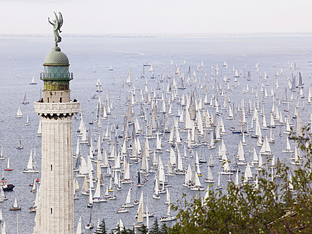 Italy, Sailing boats racing across Gulf of Trieste in annual boat race with lighthouse in foreground - BSCF000175