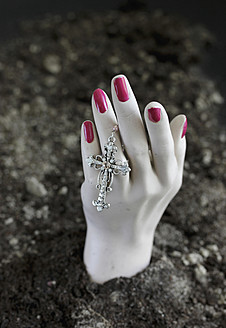 Human hand of mannequin with crucifix in soil at cemetery - HSTF000024