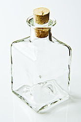 Close up of glass bottle with cork on white background - MAEF005202