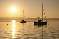 Germany, Bavaria, Sailing boat on Lake Ammersee at sunset - UMF000524