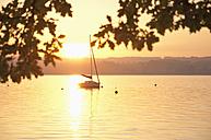 Germany, Bavaria, Sailing boat on Lake Ammersee at sunset - UMF000530