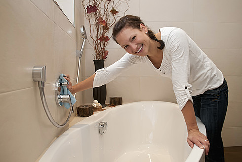 Germany, Brandenburg, Young woman cleaning bathroom, smiling, portrait - BFRF000115