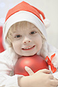 Boy holding christmas bauble, smiling, portrait - MJF000161