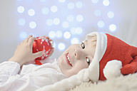 Boy holding christmas bauble, smiling - MJF000152